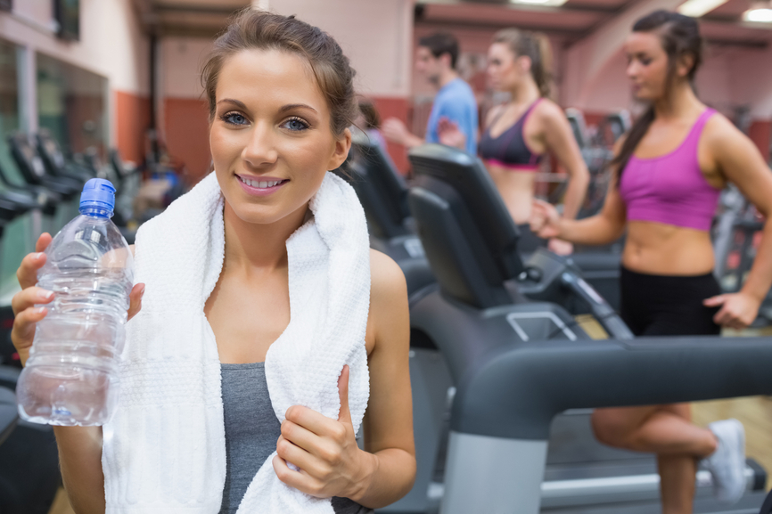 Woman smiling and drinking water in the gym so fetch daily woman smiling and drinking water in the gym sciox Choice Image